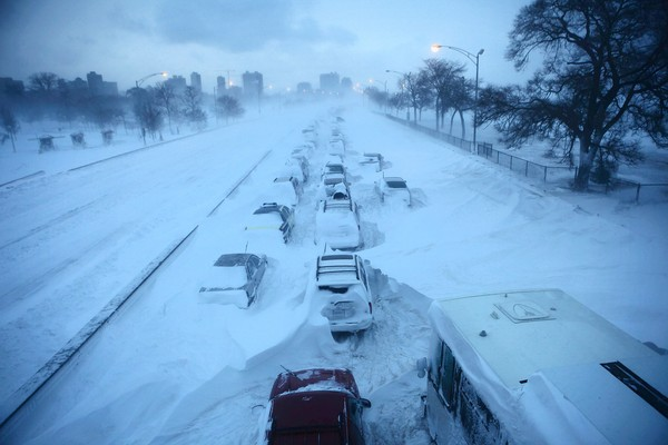 Highway of abandoned cars and snow at least to height of cars packed around them.